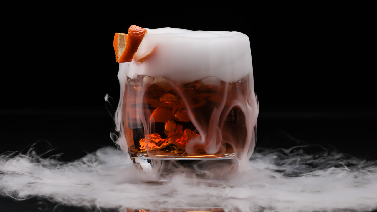 Cocktail with smoke at top and swirling around the glass